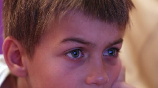 child face watching hypnotized by tv screen learning about story - solo un bambino maschio video stock e b–roll