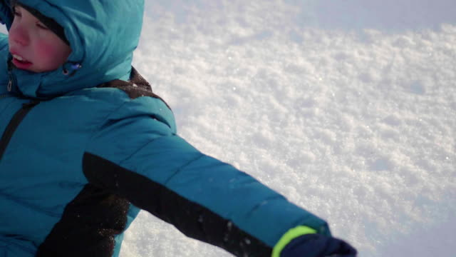 Child falls into the snow in slow motion. Active sports outdoors. Winter Sunny day video