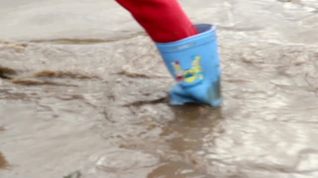 Child feet in rubber boots walk puddle dirt, construction site video
