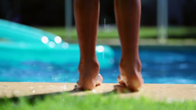 Child feet on the edge of the swimming pool jumping into water