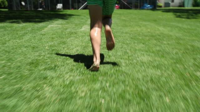 barn fötter som kör i trädgården bakgård och hoppa i pool vatten i slow-motion - gräsmatta odlad mark bildbanksvideor och videomaterial från bakom kulisserna