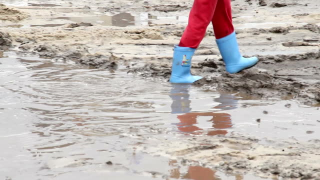 Child feet walk on puddle dirt, blue boots, children unsafety video