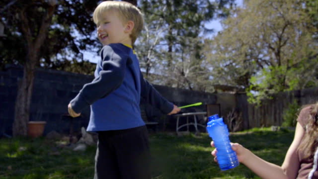 Child flicks bubble wand around in his family's backyard video