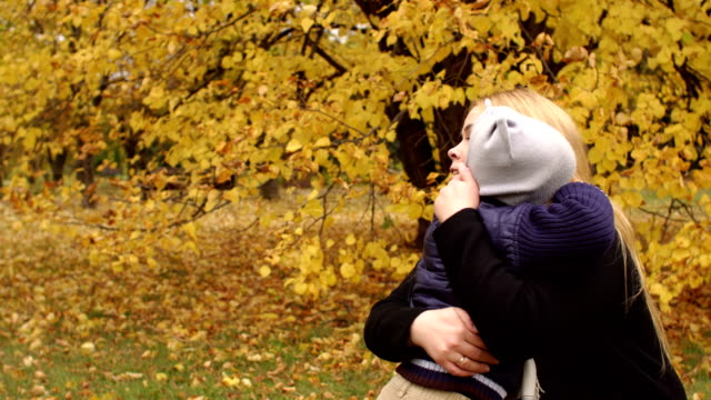 Child gently hugs her mother in the autumn Park. video