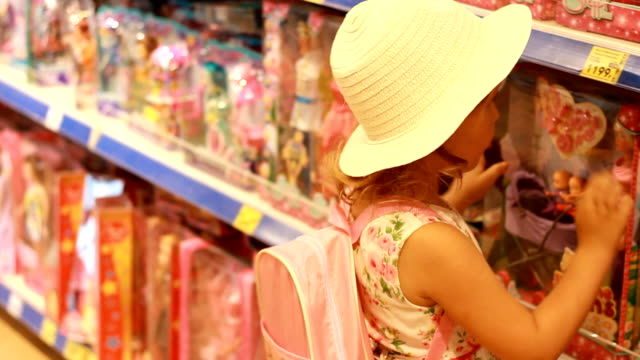 Child girl chooses a doll for himself a gift in a store for children with toys Child girl chooses a doll for himself a gift in a store for children with toys. doll stock videos & royalty-free footage