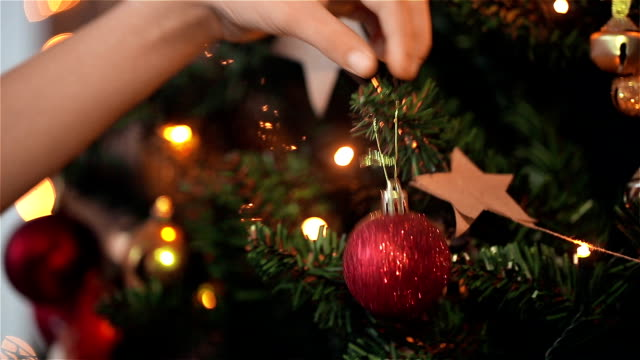Child girl decorates the Christmas tree. HD shot with slider.