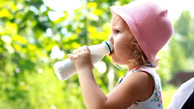 Child girl drinks a milk drink from a bottle or kefir, smiles and shows a white mustache from yogurt. video