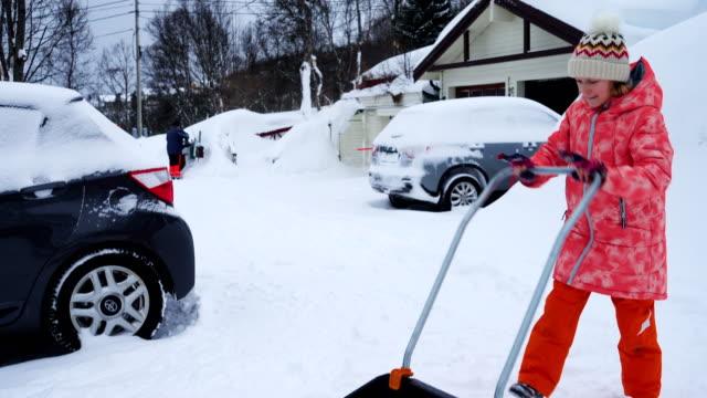 barnflicka hjälper till att rengöra en väg från snö med spade efter vintern snöstorm - skyffel bildbanksvideor och videomaterial från bakom kulisserna
