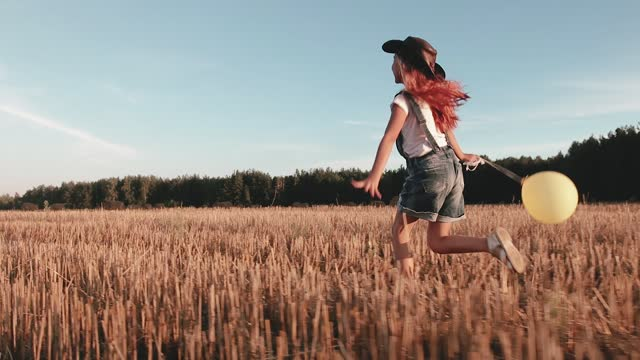 Child girl in a denim jumpsuit and a cowboy hat runs across the field