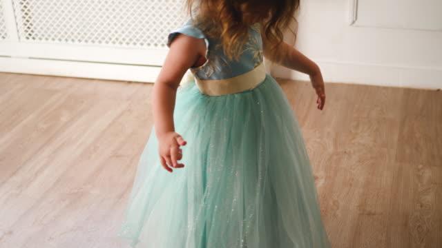 fille d'enfant dans une robe verte pose devant un photographe - Vidéo
