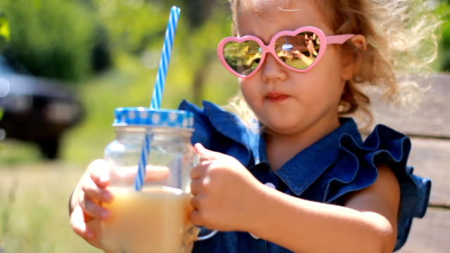 vídeos de stock e filmes b-roll de child girl in sunglasses drinks smoothies in the park on a sunny windy day - sumo