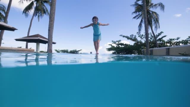 stockvideo's en b-roll-footage met kind meisje in zwemmen masker springen in zwembad zwemmen in slow motion in de tropen. - swimmingpool kids
