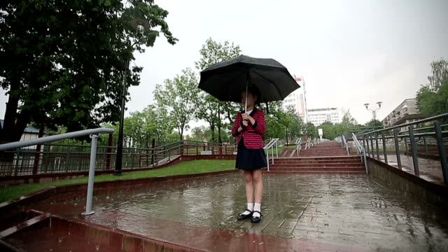 Child girl in the rain with an umbrella. Slow motion. video