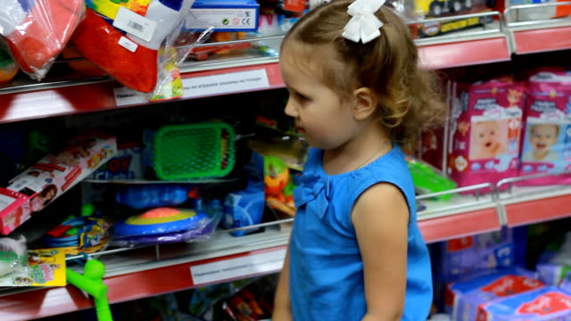 child girl in the supermarket chooses a toy for himself. baby shopping. - giocattolo video stock e b–roll