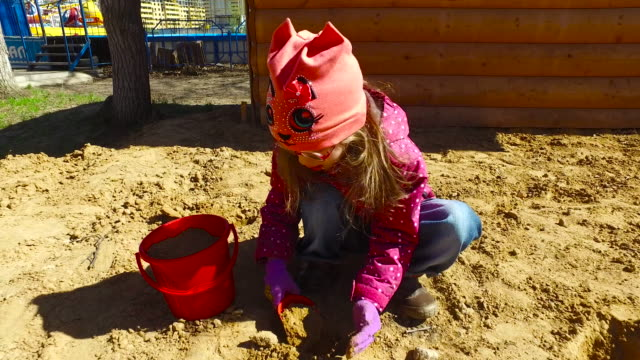 Child girl playing in the sandbox. Girl posing cake out of the sand. video