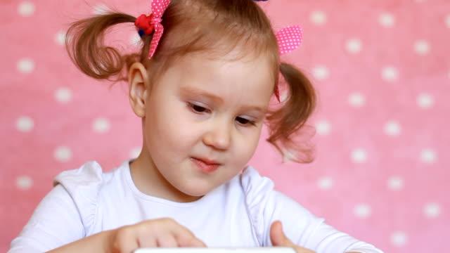 hareket eden telefon ile oynayan kız çocuk. bebek oyun uygulama smartphone üzerinde kullanır. potrait tatlı - dijital yerli stok videoları ve detay görüntü çekimi