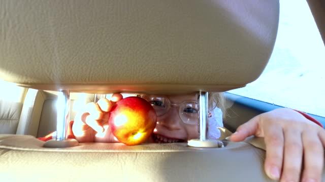 bambino ragazza gioca in auto. la ragazza completati mangia. piove. - pesche bambino video stock e b–roll