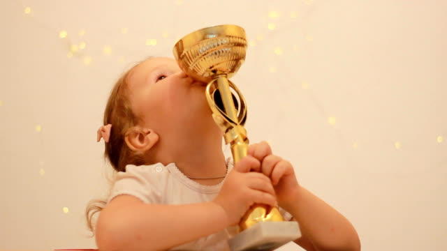 Child girl rejoices in the victory and reward, kisses and hugs the winner's cup for the first place in the championship competition video
