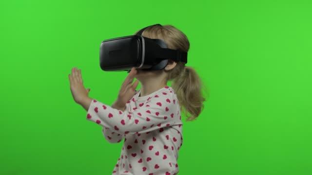 Child girl using VR headset helmet to play game. Watching virtual reality 3d 360 video. Chroma key