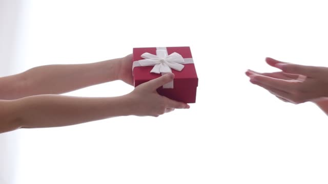 A child gives mom a small gift in a red box with a white bow