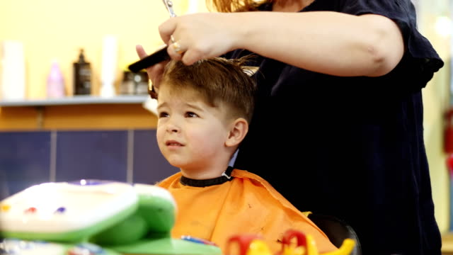 Child Hairstyle Hairdresser Working With Small Boy In Barbershop