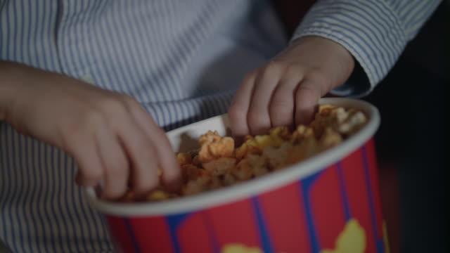 vídeos de stock, filmes e b-roll de mão de criança levar pipoca de caixa de papel no cinema. crianças levar pipoca de caramelo - balde pipoca