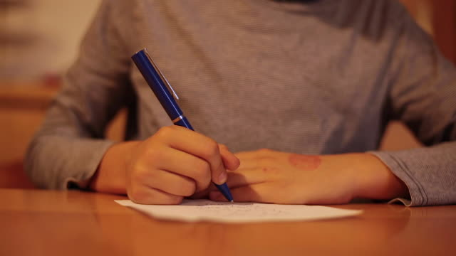 Child hands writing a letter