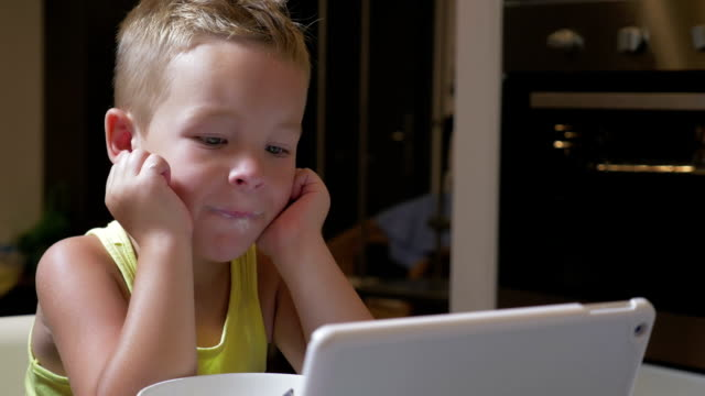 Child having meal with cartoons on pad video