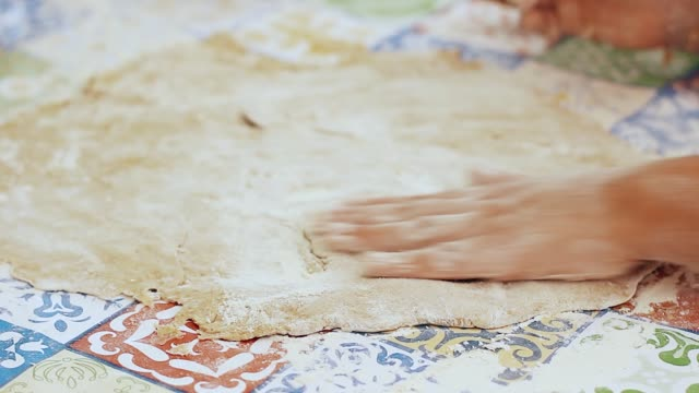 child helping at home passing flour in homemade pizza dough
