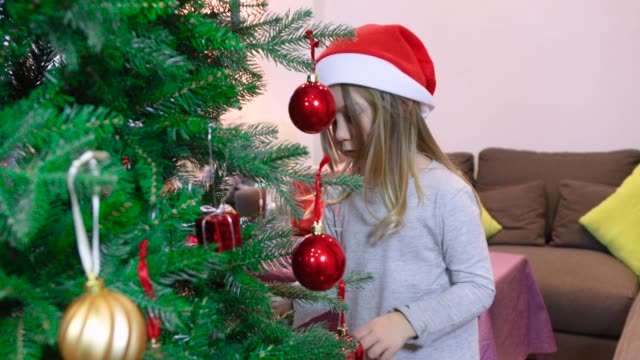 child holding christmas balls in tree video