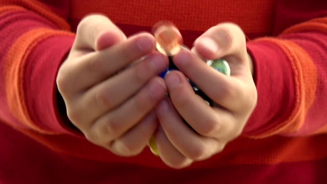 Child holding colorful marbles in his hands. video