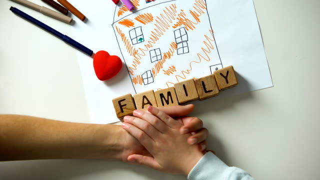 Child holding hand of adult person, family word made from cubes on house picture