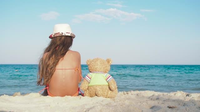 Child holding teddy bear on beach.