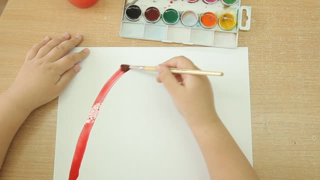 A child holds a brush in his right hand and draws a rainbow on a white sheet of paper.