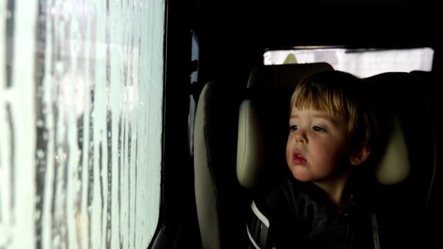 child in a car seat at the car wash