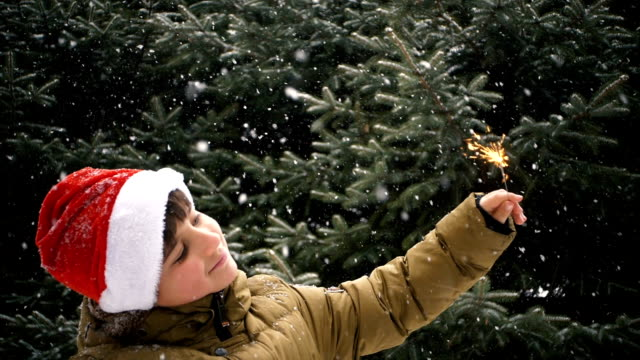 child in a Christmas hat near a Christmas tree with a Bengal fire video