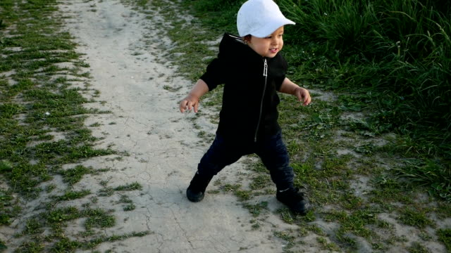 child in a jacket with a hood and a cap runs in the field along video
