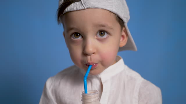 child in a white shirt and cap drinks kefir from a bottle - paglia video stock e b–roll