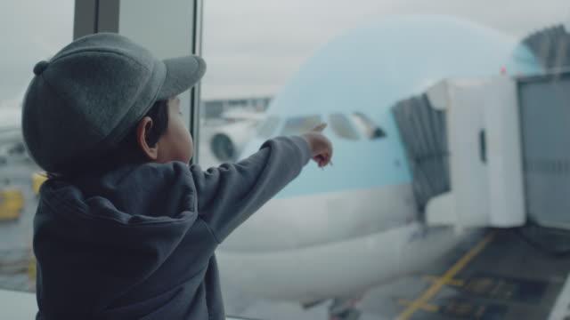 stockvideo's en b-roll-footage met kind in luchthaven dichtbij venster op zoek op vliegtuigen en wachten tot de tijd van de vlucht - raam bezoek