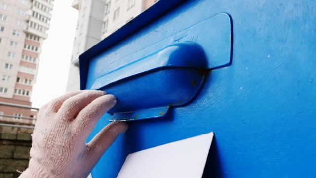 A child in gloves throws a letter in a blue mail box.