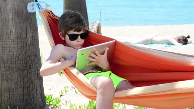 Child in hammock on the beach uses tablet while his mother is stretched in the sand
