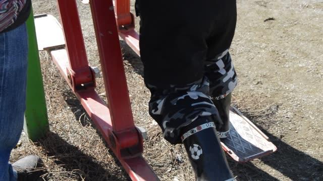 ett barn i overaller och gummistövlar vill göra på egen hand på en gata simulator, faller, men fortsätter att träna. bakåtvy, vårdag - lucia bildbanksvideor och videomaterial från bakom kulisserna