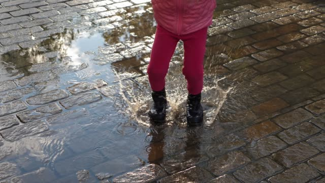 Child in pink jumps on puddles, splashes scatter from rubber boots, slow motion. video