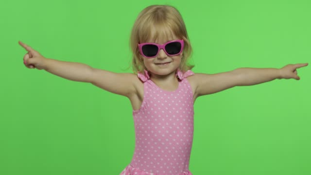 Child in pink swimsuit doing sports exercises, girl fitness training and dancing