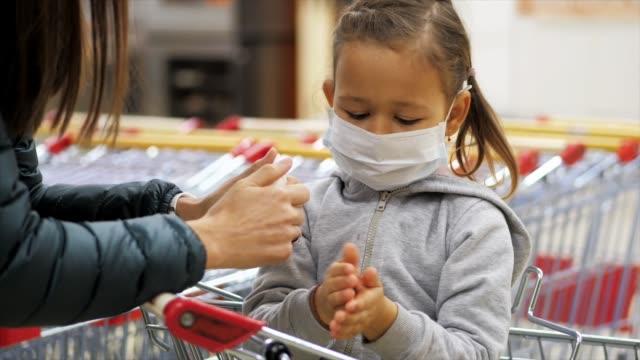 koruyucu maskeli çocuk markette dezenfekte ile ellerin dezenfeksiyonuna neden olur. - maske stok videoları ve detay görüntü çekimi