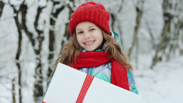 Child in red hat with Christmas presents and gifts in snow. Winter outdoor fun. Kid play in snowy park on Xmas eve. Happy Little caucasian girl smile and holding gift box