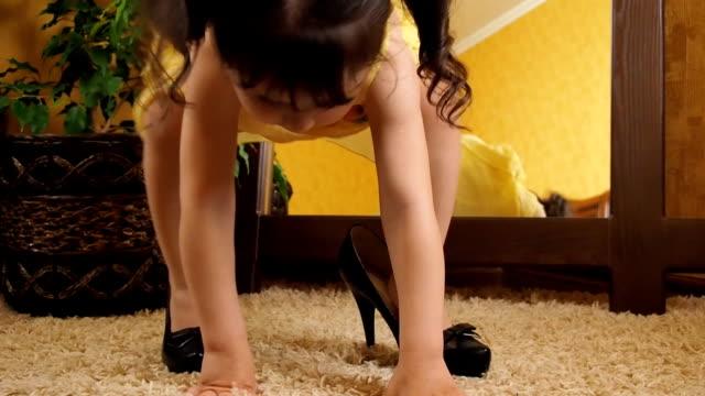vídeos de stock, filmes e b-roll de uma criança em sapatos para adultos - salto alto