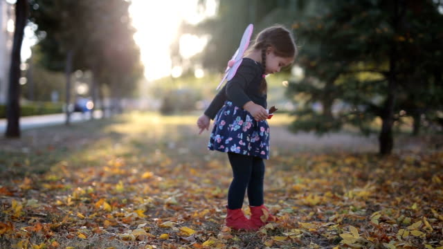 Child in the park eating candy Cute child in the park in autumn, having fun and eating candy. dressing up stock videos & royalty-free footage