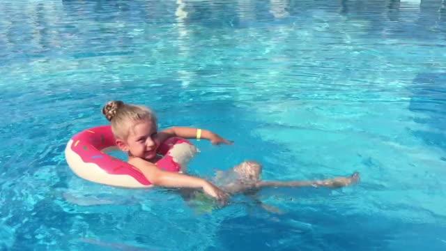 vídeos de stock, filmes e b-roll de criança na piscina. uma garotinha está nadando na piscina. - boia salva vidas