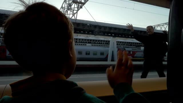 子供列車を残して彼の祖父母に振っている手 ビデオ